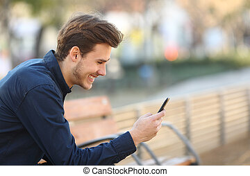 Happy guy using a smart phone in a park