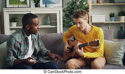 Happy guys African American and Caucasian are learning to...