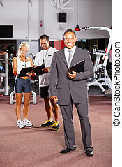 happy gym manager and trainers inside gym
