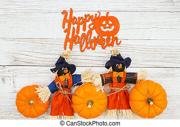 Happy Halloween greeting with orange pumpkins with fall scarecrows on weathered wood