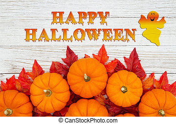 Happy Halloween greeting with red and orange fall leaves and a pumpkins on weathered wood