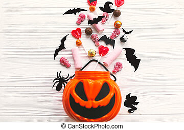 Happy Halloween. Halloween candy spilled from jack o lantern bucket with skulls, black bats, ghost, spider decorations on white wooden background, flat lay. Copy space. Trick or treat