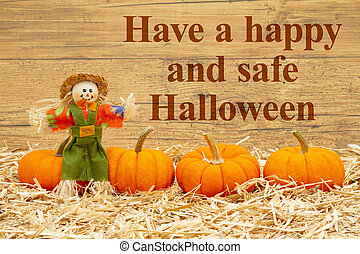 Happy Halloween message with scarecrow and orange pumpkins on straw hay