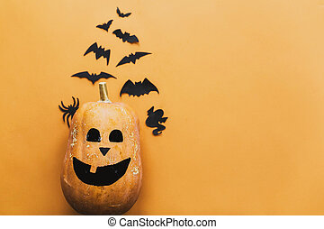 Happy Halloween. Pumpkin jack lantern and black bats, ghost, spider paper decorations on yellow background, copy space. Trick or treat concept. Halloween flat lay.