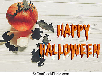 happy halloween text flat lay. pumpkin with witch ghost bats and spider black decorations on white wooden background top view with space for text. seasonal greetings