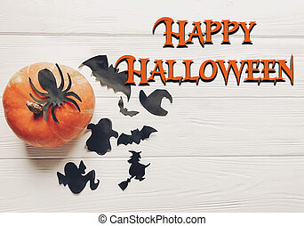 happy halloween text flat lay. pumpkin with witch ghost bats and spider black decorations on white wooden background top view with space for text. cutouts for autumn holiday