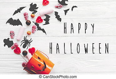 Happy Halloween text, greeting card. Halloween candy spilled from jack o lantern bucket with skulls, black bats, ghost, spider on white wooden background, flat lay.  Trick or treat