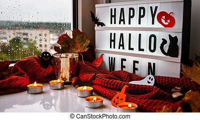 HAPPY HALLOWEEN. Text in white light box, with a background of sweater, dried leaves halloween autumn decoration on the windowsill. Rainy window. Ghost, pumpkins bat, black cat.