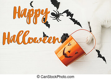 Happy Halloween text on cat paw holding Jack o lantern candy pail on white background with bats and spider decorations, top view. Trick or treat. Handwritten sign, seasonal greeting card
