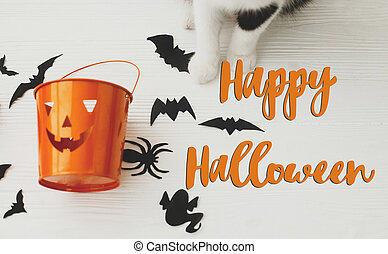 Happy Halloween text on cat paws holding Jack o lantern candy pail on white background with bats and spider decorations, top view. Trick or treat. Handwritten sign, seasonal greeting card