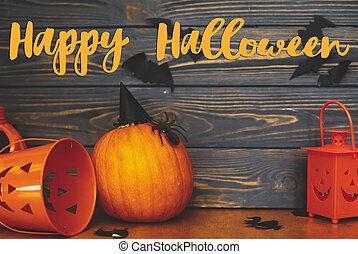 Happy Halloween text on pumpkin with spider and witch hat, Jack o lantern candy bucket and bats on dark background. Handwritten sign, seasonal greeting card