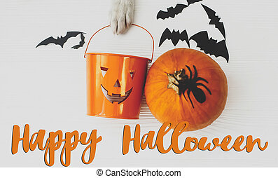 Happy Halloween text on puppy holding Jack o lantern candy pail on white background with pumpkin, bats and spider decorations, top view. Trick or treat. Handwritten sign, seasonal greeting card