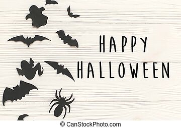 Happy Halloween text sign, flat lay. Black paper bats, spiders, ghosts top view on white rustic wooden background. Space for text. Season's greeting card