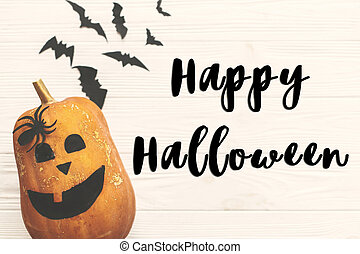 Happy Halloween text sign, flat lay. Halloween pumpkin Jack o Lantern with bats, spiders top view on white rustic wooden background. Season's greeting card