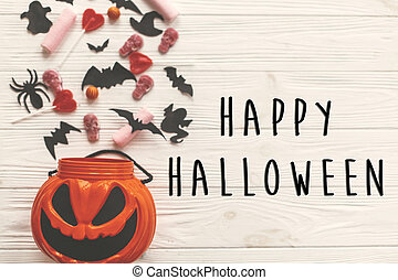 Happy Halloween text sign, flat lay. Jack o Lantern bucket with holiday candy, bats, spiders, skulls on white rustic wood. Space for text. Season's greeting card