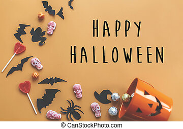Happy Halloween text sign, flat lay. Jack o Lantern bucket with holiday spilling candy, bats, spiders, skulls on orange paper. Space for text. Season's greeting card