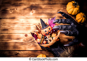 Happy Halloween. Werewolf or zombie hands making scary pumpkin gift for trick or treat party. copy space for text