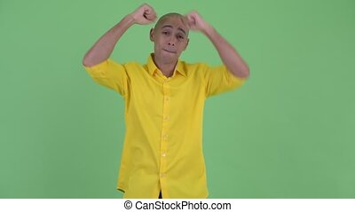 Happy handsome bald businessman dancing - Studio shot of...