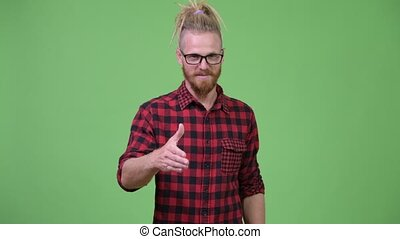 Happy handsome bearded hipster man with dreadlocks giving...