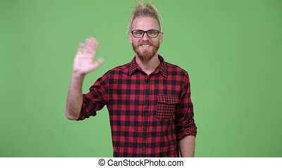 Happy handsome bearded hipster man with dreadlocks greeting...