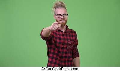 Happy handsome bearded hipster man with dreadlocks pointing...