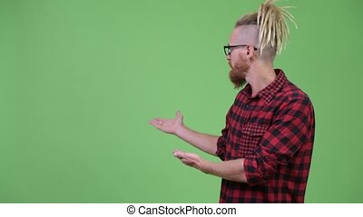 Happy handsome bearded hipster man with dreadlocks showing...
