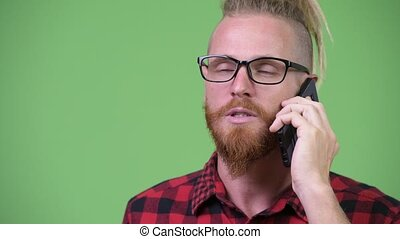 Happy handsome bearded hipster man with dreadlocks talking on the phone