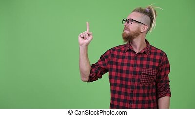 Happy handsome bearded hipster man with dreadlocks thinking while pointing up