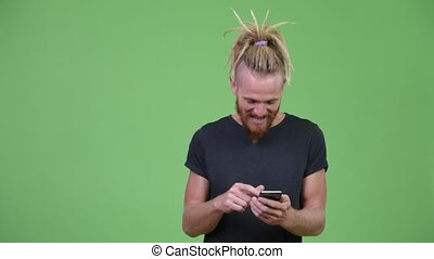 Happy handsome bearded man with dreadlocks using phone and getting good news
