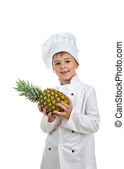 Happy handsome boy wearing chef uniform holding ananas.