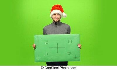 Happy handsome brutal man in Christmas hat. green screen,...