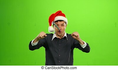 Happy handsome brutal man in Christmas hat. green screen