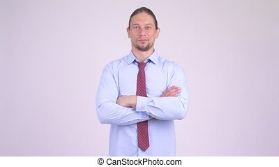 Happy handsome businessman laughing with arms crossed