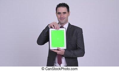 Happy handsome businessman showing digital tablet