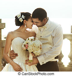 Happy handsome groom and beautifyl bride hugging on balcony at sunset sea background
