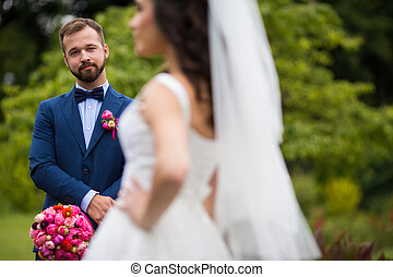 Happy handsome groom with bouquet looking beautiful bride outdoors