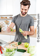 Happy handsome guy cooking salad with laptop