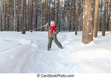Happy handsome little boy with red scarf poses on ski in forest at sunny day