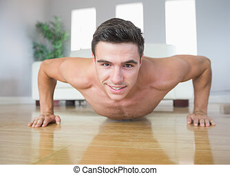 Happy handsome man doing push ups