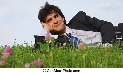 happy handsome man lying and falling on green grass