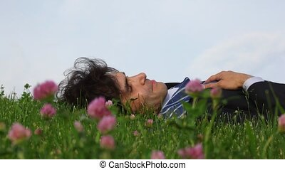 happy handsome man lying on green grass and field flowers