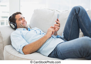 Happy handsome man lying on sofa using tablet and listening...