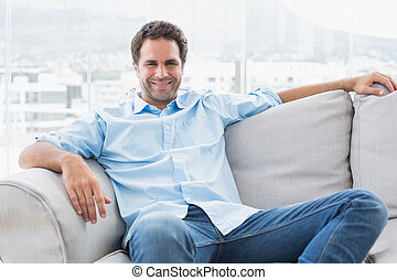 Happy handsome man relaxing on the couch looking at camera