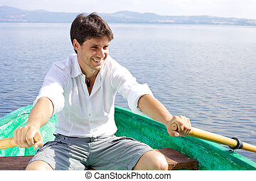 Happy handsome man rowing on a lake - Smiling male model ...