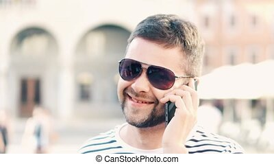 Happy handsome man talking on his cell phone on the street, close-up shot
