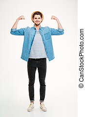 Happy handsome young man standing and showing biceps