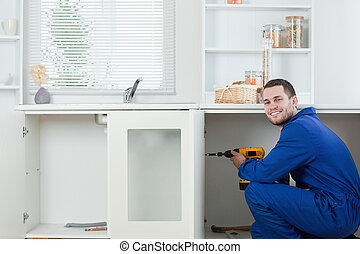 Happy handyman fixing a door in a kitchen
