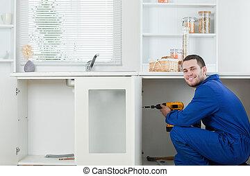 Happy handyman fixing a door in a kitchen