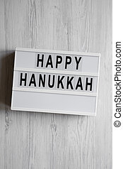 'Happy Hanukkah' word on modern board over white wooden background, overhead view. From above, flat lay, top view.