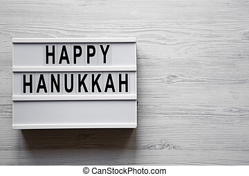 'Happy Hanukkah' word on modern board over white wooden background, top view. From above, flat lay, overhead.